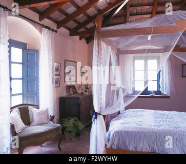 Four poster bed with white mosquito net in rustic Spanish country bedroom - Stock Photo