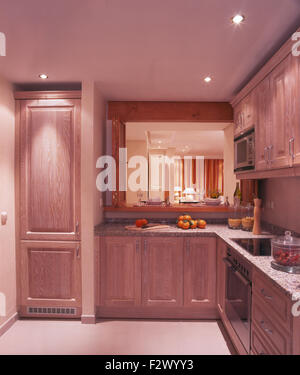 Recessed lighting in modern Spanish kitchen with a hatch and fitted cupboards with wooden doors - Stock Photo