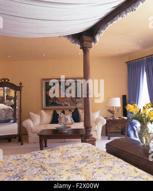 Four poster bed and cream sofa in Spanish country bedroom - Stock Photo