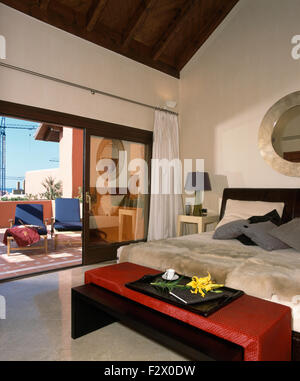 Red stool below bed with faux fur throw in modern Spanish bedroom with open glass doors to patio - Stock Photo