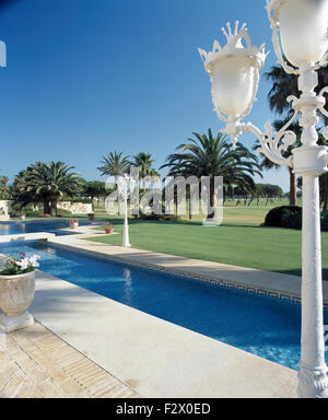 Tall lamps beside rectangular blue pool in grounds of Spanish villa - Stock Photo