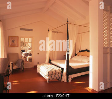 Upholstered ottoman stool below four poster bed with white drapes in white Spanish coastal bedroom - Stock Photo
