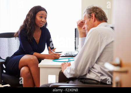 Female Doctor Treating Patient Suffering With Depression - Stock Photo