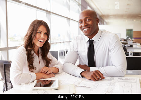 Male and female architects at work, looking to camera - Stock Photo