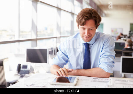 Male architect using tablet computer at a desk in an office - Stock Photo