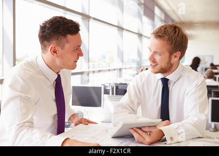 Two young male architects in discussion at an office desk - Stock Photo