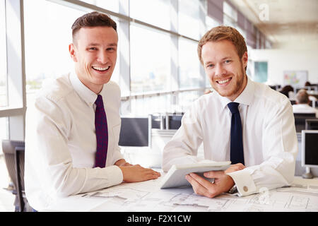 Two young male architects working together, look to camera - Stock Photo