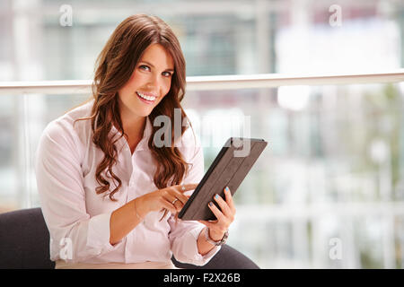 Young businesswoman using tablet computer looking to camera - Stock Photo