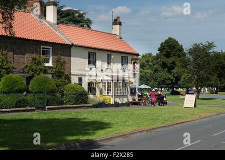 Women walk by attractive, traditional, English rural pub (Lord Collingwood) - sunny summer day, Upper Poppleton - Stock Photo