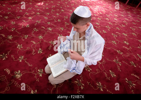 Young uniformed Karaite Jew bowing on the knees during prayer in a Karaite synagogue in the city of Ramle or Ramleh - Stock Photo