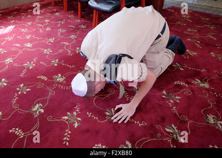 Young uniformed Karaite Jew bowing on the knees and prostrate during prayer in a Karaite synagogue in the city of - Stock Photo