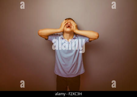boy teenager European appearance in a blue shirt brown hair closed eyes with his hands on a gray background shouts - Stock Photo