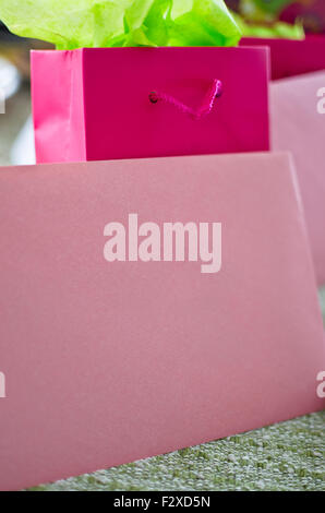 Blank pink envelope and gift bag with pretty bright green tissue paper. - Stock Photo