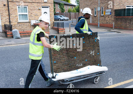 Construction workers transporting sheet of glass, Green Dragon Lane, Brentford, Greater London, England, United - Stock Photo