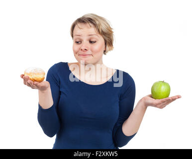 Young woman holding a donut and an apple and being more attracted by the donut, isolated on white - Stock Photo