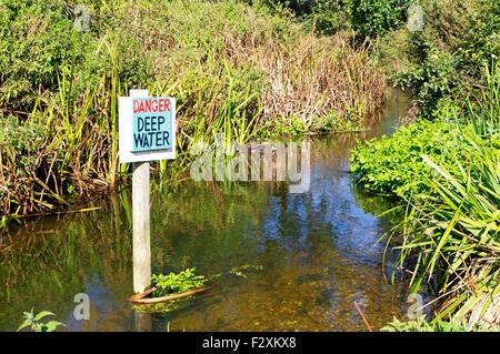 Danger - Deep Water sign in the River Glaven at Glandford, Norfolk, England, United Kingdom. - Stock Photo
