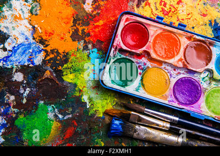 Desk of an artist with watercolor paints and paintbrushes.