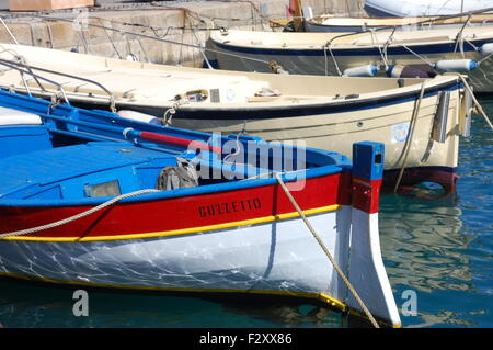 Colourful red, blue and white rowing boat in the port at Porto Santo Stefano, Monte Argentario, Italy. - Stock Photo