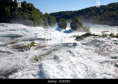 Water cascading turbulently over the Rheinfall near the town of Schaffhausen in Switzerland - Stock Photo