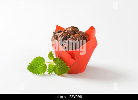 Double chocolate chip muffin wrapped in red paper - Stock Photo