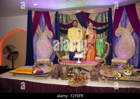 Bangladeshi bride  and groom at their wedding reception waiting to greet their families & guests in Brooklyn, NY. - Stock Photo
