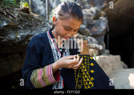 Girl of the ethnic 'black Hmong' tribe embroider traditional clothing - Stock Photo
