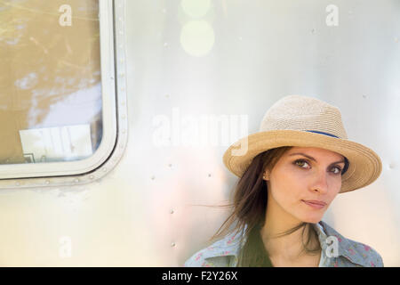 A young woman wearing a hat sitting in the shade of a silver coloured trailer. - Stock Photo
