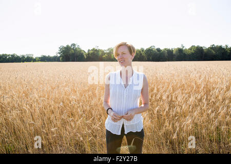 Half length portrait of a young woman standing in a cornfield. - Stock Photo