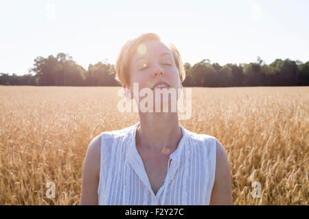 Head and shoulders portrait of a young woman standing in a cornfield. - Stock Photo