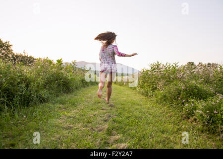 A woman running along a path in a meadow. - Stock Photo