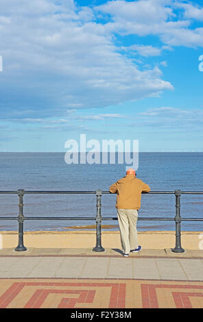 Middle-aged man on promenade, gazing out to sea, Cleethorpes, Lincolnshire, England UK - Stock Photo