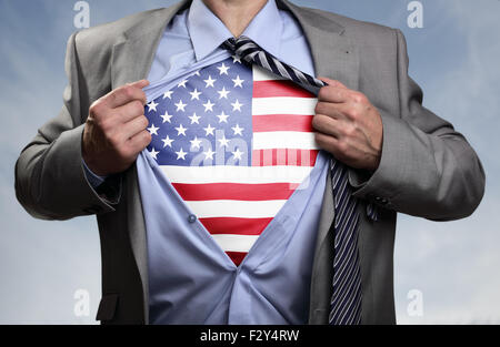 Superhero businessman revealing American flag - Stock Photo
