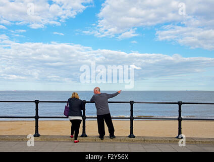 Man and woman, pointing out to sea, Cleethorpes, Lincolnshire, England UK - Stock Photo