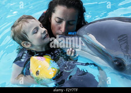 Alushta, Russia. 24th Aug, 2015. A child swimming with a dolphin as part of a therapy in the Akvarel dolphinarium. - Stock Photo