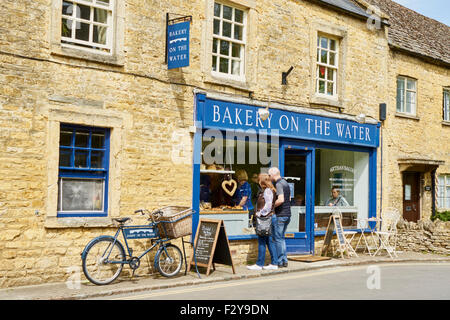 Bakery shop, people and bakers bike outside. - Stock Photo