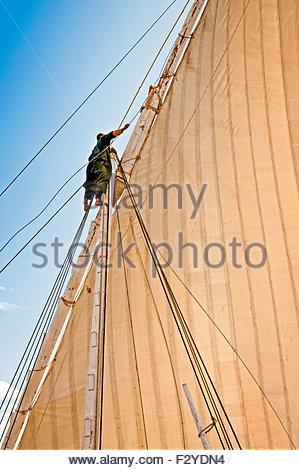 LUXOR, EGYPT – NOVEMBER 28, 2011: A crew member adjusting the sail of a dahabiya sailing on the river Nile Egypt. - Stock Photo