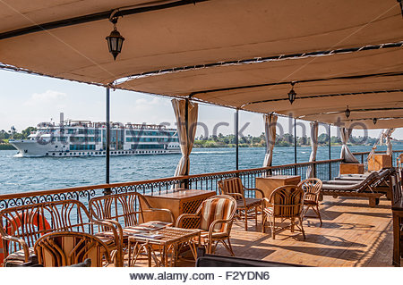 LUXOR, EGYPT – NOVEMBER 28, 2011: A view of a large tourist ship from a dahabiya sailing on the river Nile Egypt. - Stock Photo