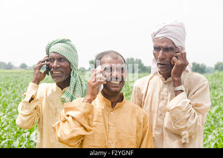 3 indian rural farmer farm Talking Mobile Phone - Stock Photo