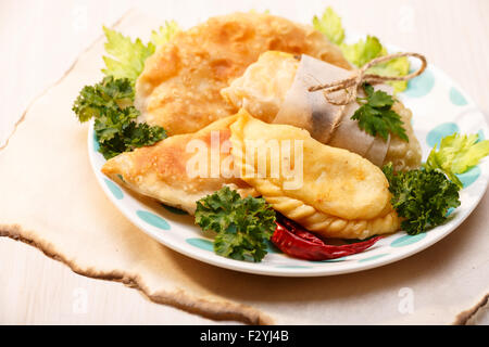 Cheese empanadas (savory patties) on wooden table. Selective focus, lit to resemble direct sunlight - Stock Photo