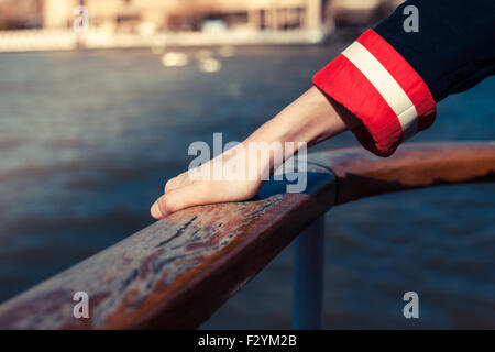 Closeup on a woman's hand holding the railing on the deck of a ship - Stock Photo