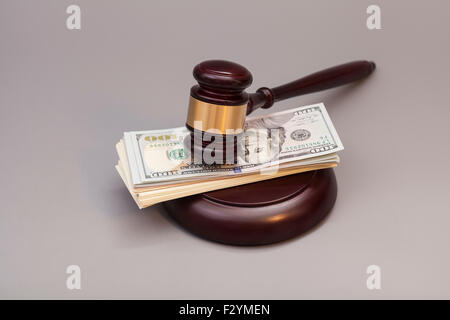 Law gavel on a stack of dollars isolated on gray - Stock Photo