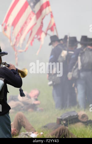 Wounded Confederate Civil War reenactor lying in front of standing Union reenactors at the anniversary of the 150th - Stock Photo