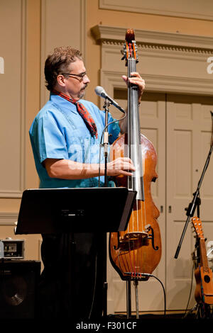 Man playing electric upright Bass instrument on stage - USA - Stock Photo