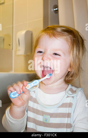 Child / baby practising brushing her teeth with a toothbrush / tooth brush for the first time. - Stock Photo