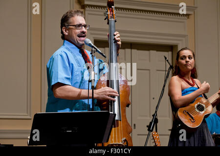 Man singing and playing electric upright Bass instrument on stage - USA - Stock Photo