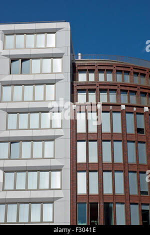 Two modern office buildings in Berlin with silver shutters - Stock Photo