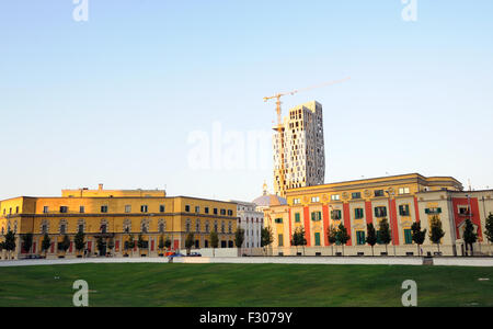 A new skyscraper rises above the ministry buildings surrounding  Skanderbeg Square, Tirana, Albania. - Stock Photo