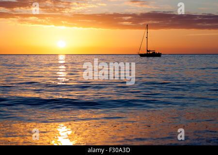 A Yacht on the west coast horizon at sunset near Aberystwyth Ceredigion West Wales UK - Stock Photo