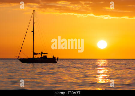 silhouette of a yacht at sunset over cardigan bay Aberystwyth Ceredigion West coast of  Wales UK - Stock Photo