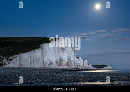 A supermoon rising over the Seven Sisters in Sussex, part of the South Downs National Park in the UK - Stock Photo